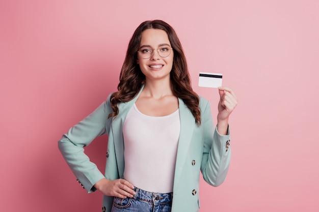 Jovem e linda mulher de negócios demonstra cartão de crédito em fundo rosa
