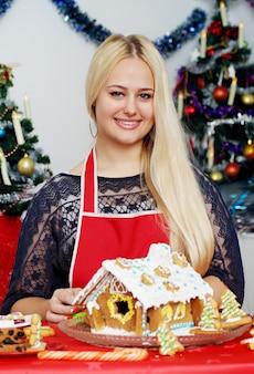 Jovem e linda mulher decorando casa de pão de gengibre