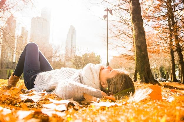 Jovem e linda mulher deitada no parque brilhante