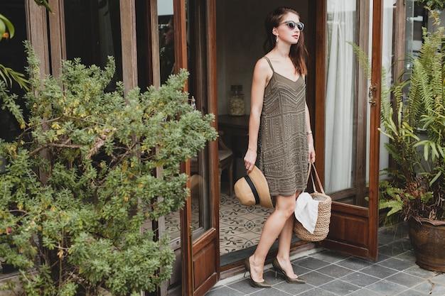 Jovem e linda mulher elegante em um hotel resort, usando um vestido moderno, estilo safári, chapéu de palha, férias de verão, roupa boêmia, bolsa de praia, óculos de sol