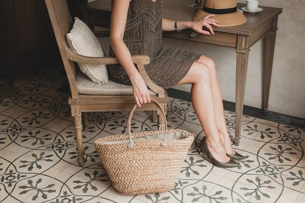 Jovem e linda mulher elegante em um quarto de hotel de resort, sentada à mesa, usando um vestido da moda, estilo safári, chapéu de palha, férias de verão, roupa boêmia, bolsa de praia, close-up de detalhes