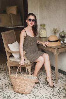 Jovem e linda mulher elegante em um quarto de hotel de resort, sentada à mesa, usando um vestido da moda, estilo safári, chapéu de palha, sorrindo, feliz, férias de verão, roupa boêmia, bolsa de praia, óculos de sol, pernas