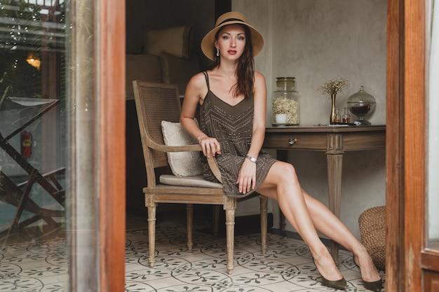 Jovem e linda mulher elegante em um quarto de hotel de resort, sentada à mesa, usando um vestido da moda, estilo safári, chapéu de palha, sorrindo, feliz, férias de verão, roupa boêmia