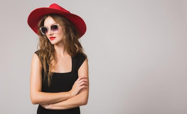 Jovem e linda mulher elegante em um vestido preto, chapéu vermelho, óculos escuros, batom vermelho, feliz, sorridente, sexy, elegante