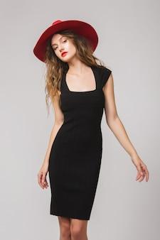Jovem e linda mulher elegante em um vestido preto e chapéu vermelho