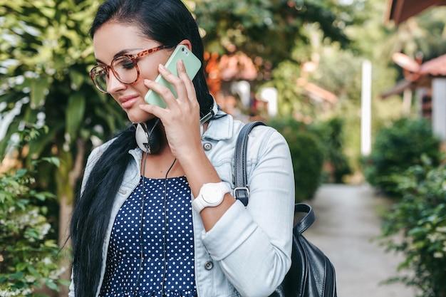 Jovem e linda mulher elegante falando no smartphone, fones de ouvido, óculos, verão, roupa jeans vintage, sorrindo, feliz, positiva