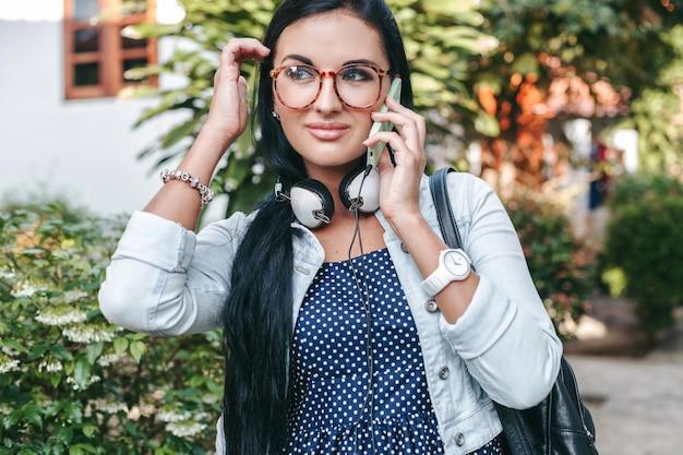 Jovem e linda mulher elegante falando no smartphone, segurando uma mochila, estilo jeans vintage, sorrindo, feliz, verão