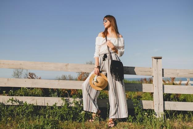 Jovem e linda mulher elegante, tendência da moda primavera verão, estilo boho, chapéu de palha, fim de semana no campo, ensolarado, sorridente, divertido, óculos de sol, bolsa preta, calças listradas