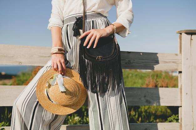 Jovem e linda mulher elegante, tendência da moda primavera-verão, estilo boho, chapéu de palha, fim de semana no campo, ensolarado, sorrindo, diversão, óculos de sol, bolsa preta, calças listradas, detalhes, acessórios