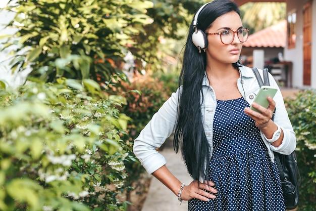 Jovem e linda mulher elegante usando smartphone, fones de ouvido, óculos, verão, roupa jeans vintage, sorrindo, feliz, positiva