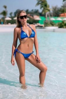 Jovem e linda mulher em pé na água azul de uma piscina tropical