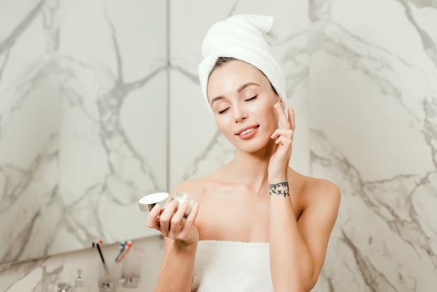 Jovem e linda mulher envolvida em toalhas aplica creme na bochecha perto do espelho