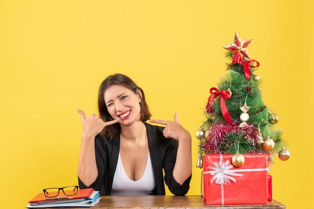 Jovem e linda mulher fazendo um gesto de me ligar, sentada em uma mesa perto da árvore de natal decorada no escritório em amarelo