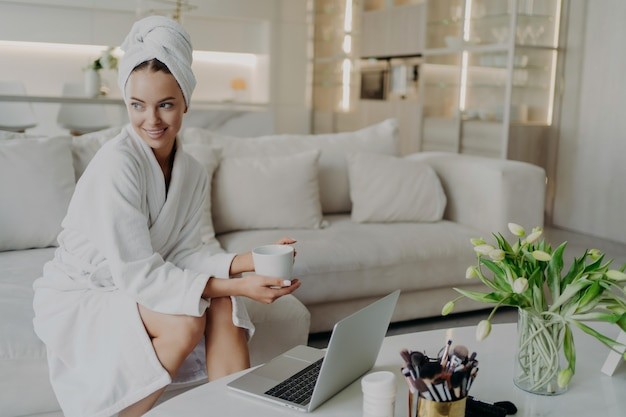 Jovem e linda mulher feliz em um roupão de banho com uma xícara de chá ou café, sentindo-se relaxada depois de tomar banho ou tomar banho em casa, sentada no sofá na sala de estar e olhando para o lado enquanto trabalha no laptop