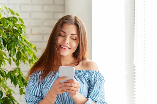 Jovem e linda mulher feliz usando telefone inteligente.