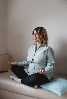 Jovem e linda mulher grávida está fazendo ioga em casa. poses de relaxamento, acalme-se, relaxe.