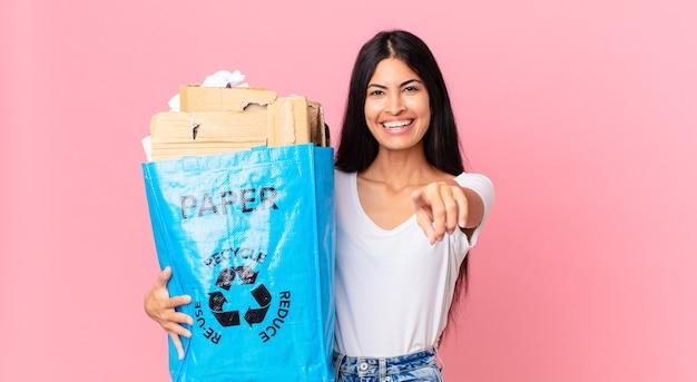 Jovem e linda mulher hispânica apontando para a câmera, escolhendo você e segurando um saco de papel para reciclar