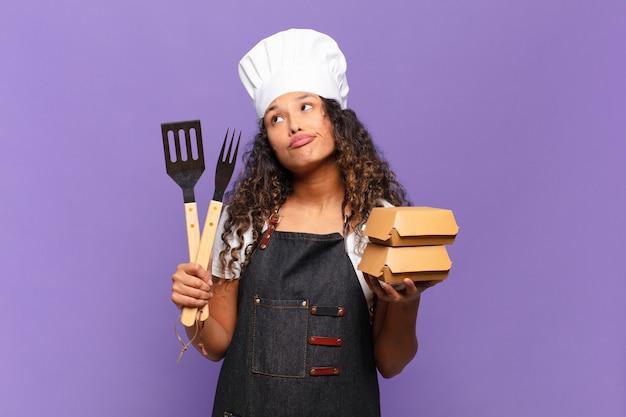 Jovem e linda mulher hispânica confundiu o conceito de chef de churrasco de expressão
