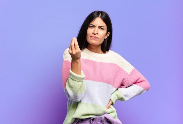 Jovem e linda mulher hispânica fazendo capice ou gesto de dinheiro, dizendo para você pagar suas dívidas!