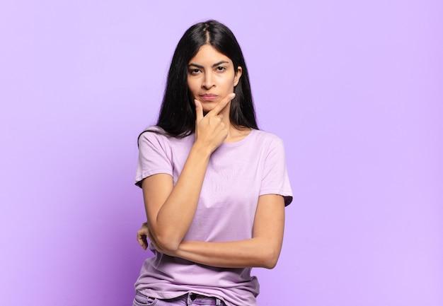 Jovem e linda mulher hispânica parecendo séria, pensativa e desconfiada, com um braço cruzado e a mão no queixo, opções de ponderação