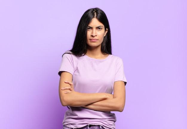 Jovem e linda mulher hispânica se sentindo descontente e desapontada, parecendo séria, irritada e com raiva de braços cruzados