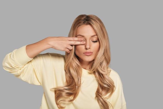 Jovem e linda. mulher jovem e atraente cobrindo os olhos com os dedos em pé contra um fundo cinza