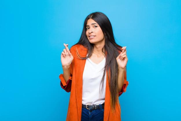 Jovem e linda mulher latina cruzando os dedos ansiosamente e esperando boa sorte com um olhar preocupado contra uma parede plana