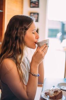 Jovem e linda mulher latina feliz com cabelo comprido encaracolado tomando um cappuccino em um café de rua