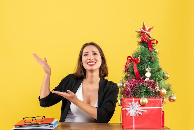 Jovem e linda mulher mostrando algo com orgulho em uma mesa perto da árvore de natal decorada no escritório em amarelo