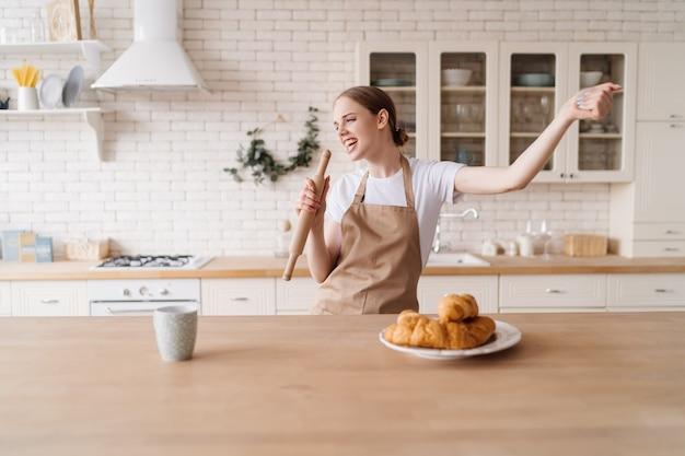 Jovem e linda mulher na cozinha de avental cantando em um rolo de massa