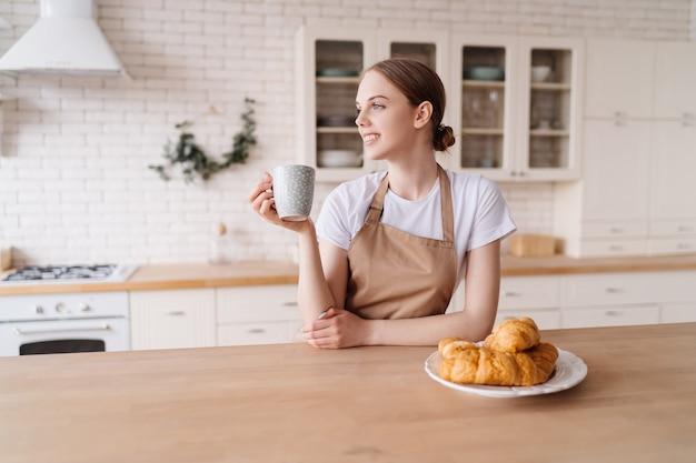 Jovem e linda mulher na cozinha de avental com café e croissant curtindo sua manhã