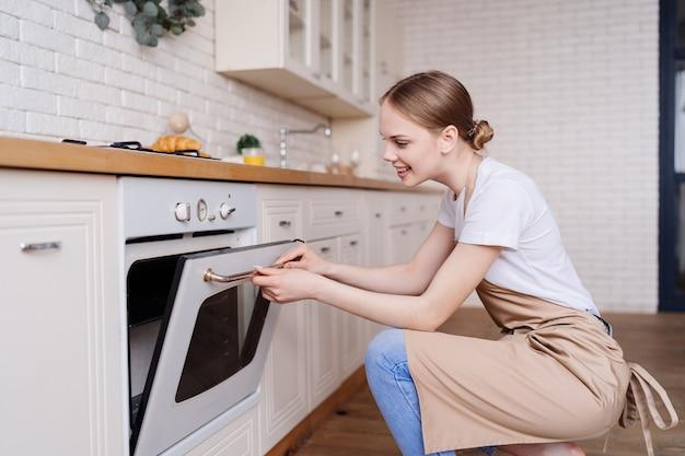 Jovem e linda mulher na cozinha usando um avental assando