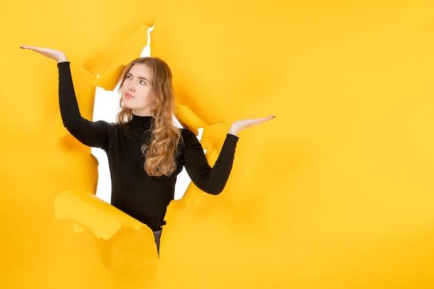 Jovem e linda mulher na parede amarela rasgada de frente