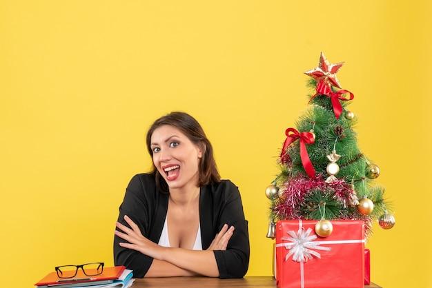 Jovem e linda mulher olhando para algo com orgulho e sentada em uma mesa perto da árvore de natal decorada no escritório em amarelo