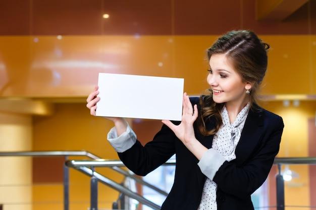 Jovem e linda mulher olhando para um cartão branco em branco