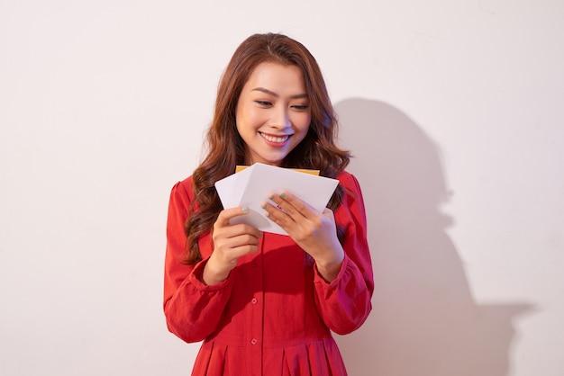 Jovem e linda mulher olhando para um cartão de convite e sorrindo