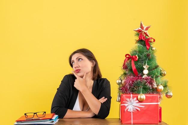 Jovem e linda mulher pensando em algo cuidadosamente sentado em uma mesa perto da árvore de natal decorada no escritório em amarelo