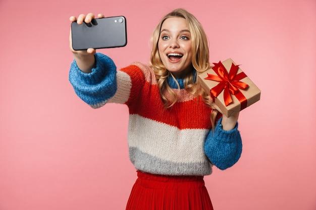 Jovem e linda mulher posando isolada sobre uma parede rosa tirar uma selfie pelo celular segurando uma caixa de presente