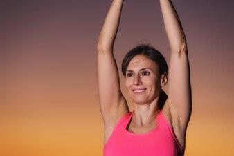Jovem e linda mulher praticando Yoga ao pôr do sol