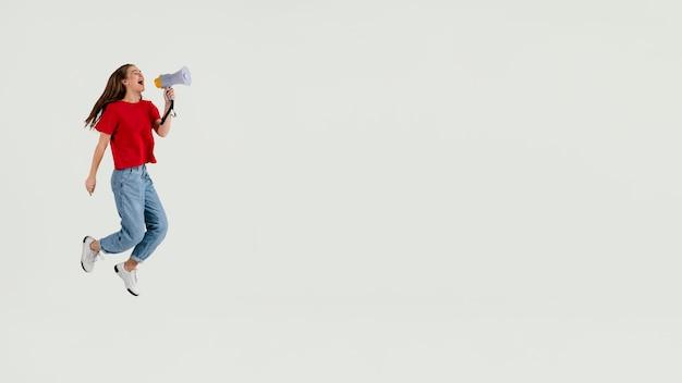 Jovem e linda mulher pulando o espaço da cópia