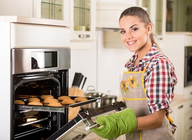 Jovem e linda mulher puxa biscoitos do forno.