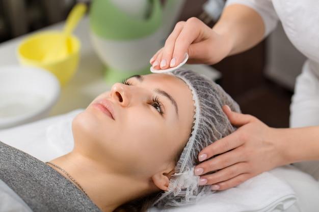 Jovem e linda mulher recebendo massagem facial