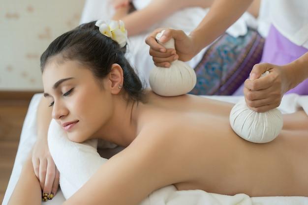 Jovem e linda mulher relaxante durante a massagem no salão de spa.