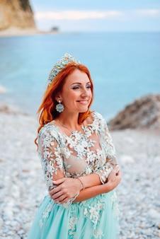 Jovem e linda mulher ruiva em um vestido luxuoso de pé em uma costa rochosa do mar adriático, close-up