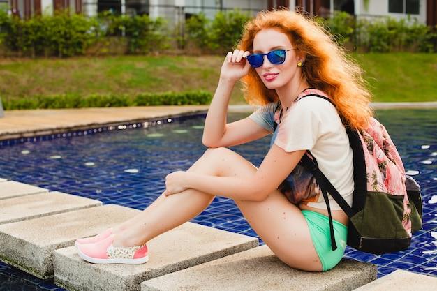 Jovem e linda mulher ruiva sentada na piscina com uma mochila, relaxada, feliz, verão, roupa descolada de hipster, shorts, camiseta, tênis, óculos de sol