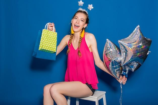 Jovem e linda mulher segurando sacolas de compras e balões