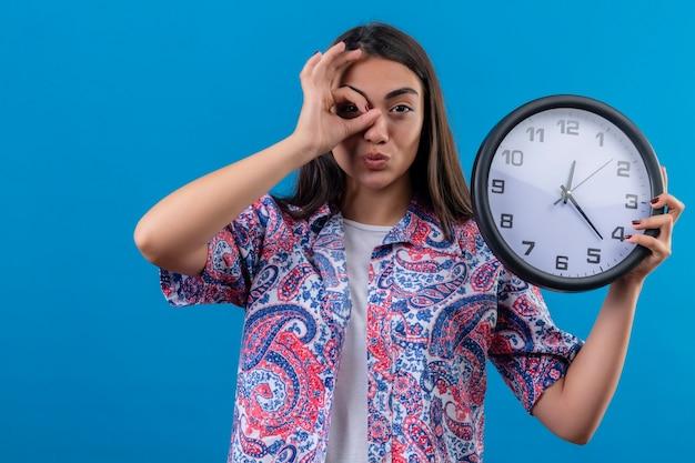 Jovem e linda mulher segurando um relógio redondo fazendo ok, cantando e olhando através desta placa se divertindo em pé sobre um fundo azul