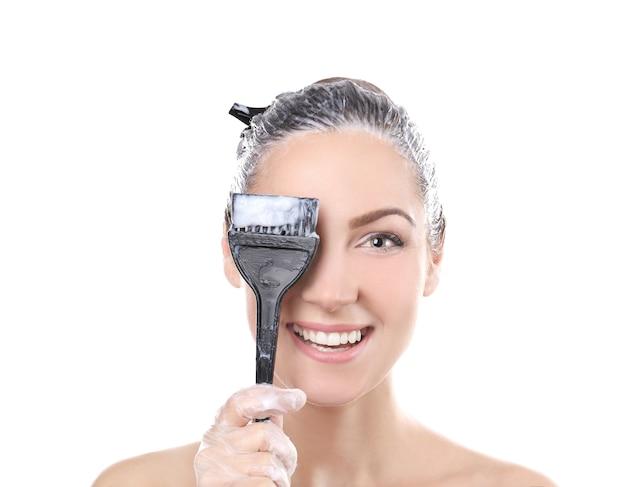 Jovem e linda mulher segurando uma escova com tintura de cabelo em fundo branco