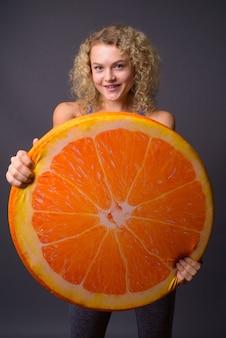 Jovem e linda mulher segurando uma grande fatia de fruta laranja