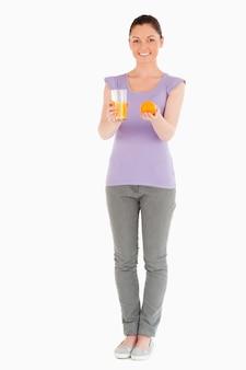 Jovem e linda mulher segurando uma laranja e um copo de suco de laranja